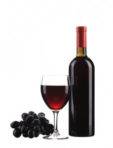 Grapes and a glass and bottle of red wine on a white background