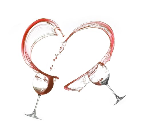 Two glasses splashing red wine into a heart shape on a white background