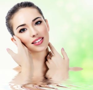 A woman with beautiful skin submerged in water to her shoulders with a green nature background