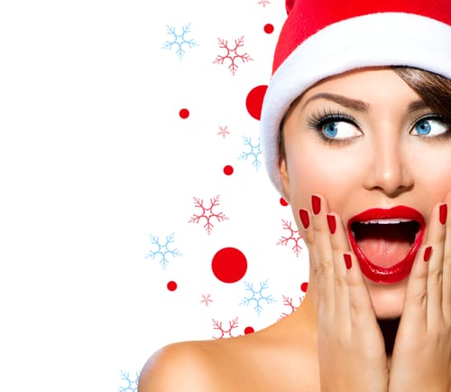 A beautiful woman in a santa hat isolated on a snowflake and red dot background
