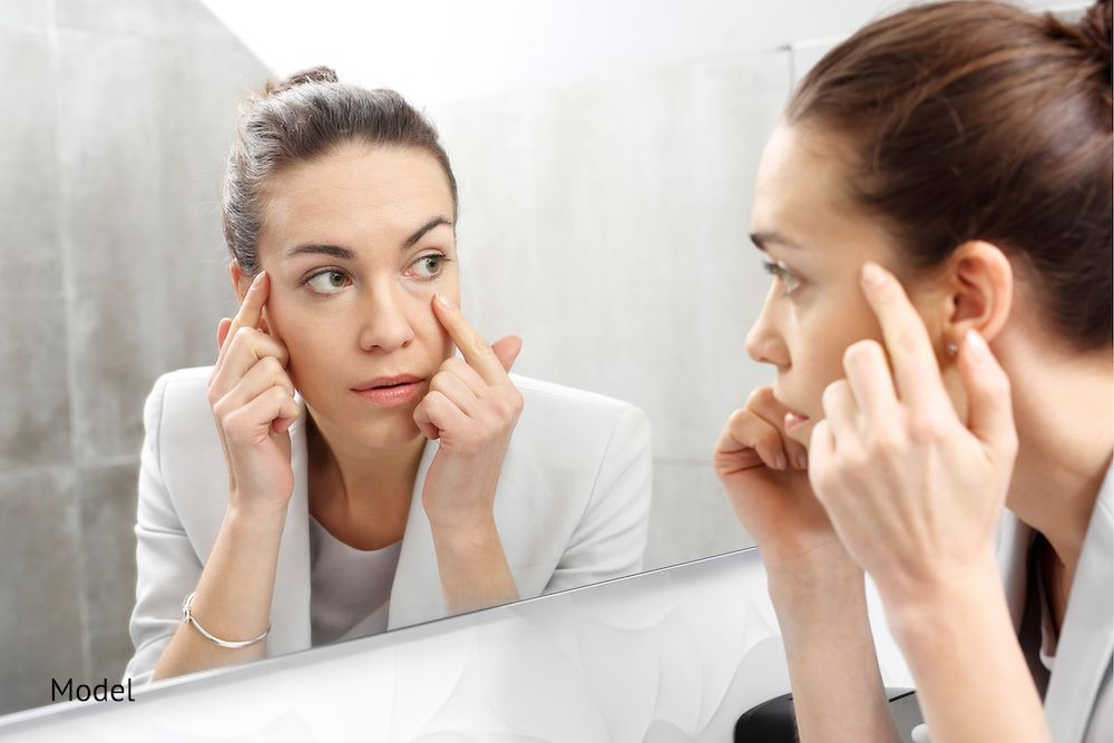 Woman looking in the mirror considering how to make her eyes look more youthful